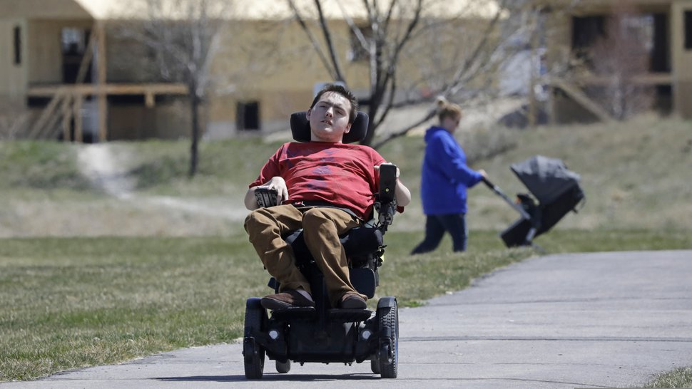 (Rick Bowmer | AP) In this April 14, 2020, photo, Jacob Hansen rides near his house, in Eagle Mountain. Even before the new coronavirus hit, cystic fibrosis meant a cold could put Hansen in the hospital for weeks. He relies on hand sanitizer and disinfecting wipes to keep germs at bay because has cerebral palsy and uses a wheelchair, but these days shelves are often bare. For millions of disabled people and their families, the coronavirus crisis has piled on new difficulties and ramped up those that already existed.