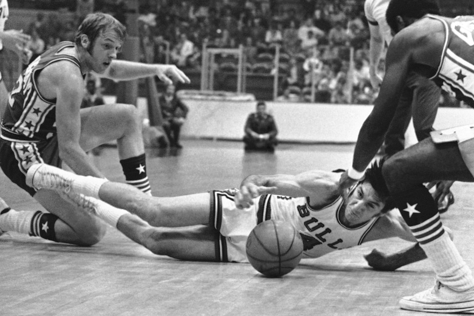 (AP Photo) Jerry Sloan (4) of Chicago Bulls reaches for the ball as he falls to court following collision in game with Philadelphia 76ers on Tuesday, Oct. 13, 1971 at Chicago. Bill Cunningham of 76ers is at left. Philadelphia won the National Basketball Association, 114-100.
