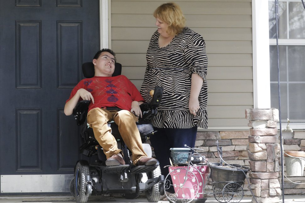(Rick Bowmer | AP) In this April 14, 2020, photo, Jodi Hansen talks with her son Jacob Hansen at their home, in Eagle Mountain, Utah. Even before the new coronavirus hit, cystic fibrosis meant a cold could put Jacob Hansen in the hospital for weeks. He relies on hand sanitizer and disinfecting wipes to keep germs at bay because has cerebral palsy and uses a wheelchair, but these days shelves are often bare. For millions of disabled people and their families, the coronavirus crisis has piled on new difficulties and ramped up those that already existed.