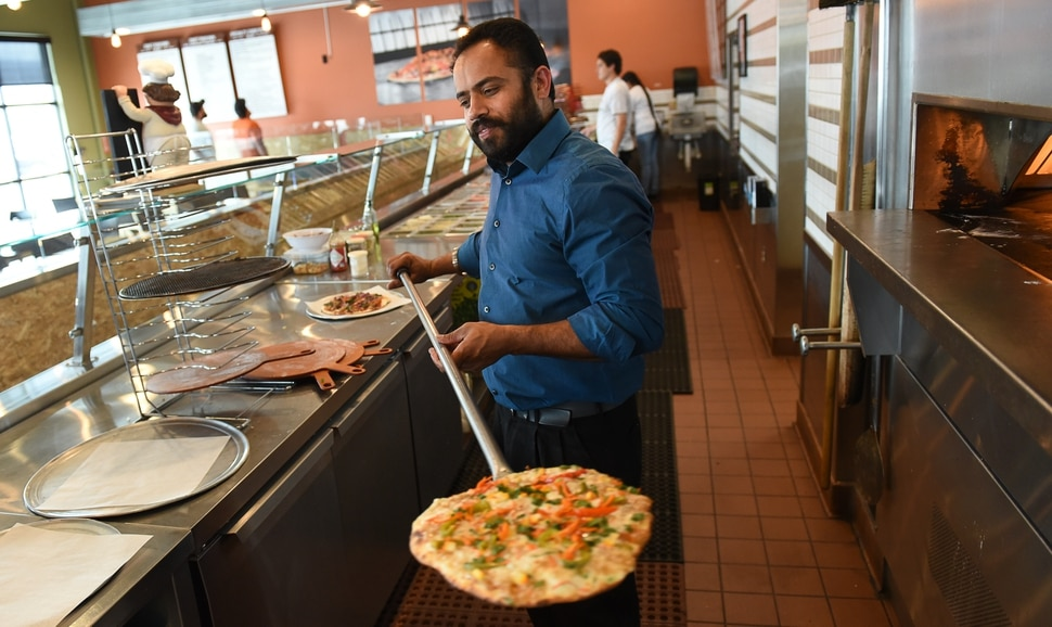 (Francisco Kjolseth | The Salt Lake Tribune) Bhinda Singh, owner of Curry Pizza, a new restaurant in West Valley City pulls out a freshly cooked pizza from the open wood fired oven. Singh has combined Italy's classic meal with the flavors and spices of India and with his second Curry Pizza restaurant proving popular, he says he's considering opening up a third location soon.