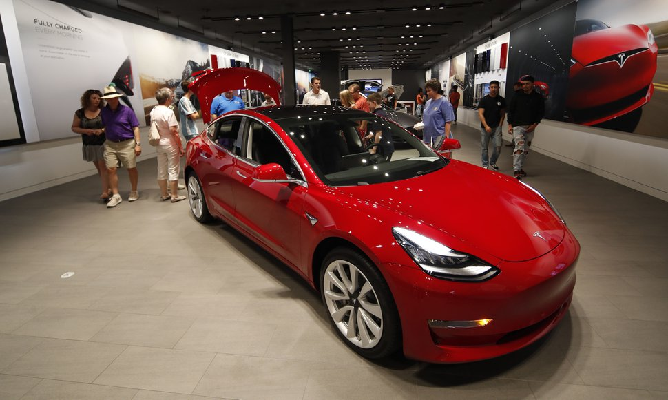 (David Zalubowski, AP file photo) In this July 6, 2018, file photo, prospective customers confer with sales associates as a Model 3 sits on display in a Tesla showroom in the Cherry Creek Mall in Denver. Tesla is suffering one of its worst sell-offs of the year after announcing it would begin closing all of its stores in favor of selling its electric cars exclusively online. The goal is to allow Tesla to lower the price of its Model 3, the vehicle that CEO Elon Musk envisions as the company's first mass-market vehicle.