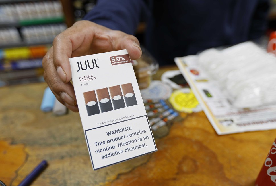 (Samantha Maldonado | AP file photo) In this June 17, 2019, photo, a cashier displays a packet of tobacco-flavored JUUL pods at a store in San Francisco.