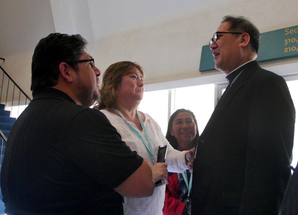 Mike Stack | for The Salt Lake Tribune Bishop Solis speaks with Irma and John Saavedra.
