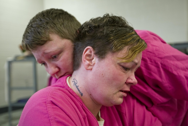 Inmate Mary Sammons, 41, foreground, is comforted in the Campbell County Jail in Jacksboro, Tenn., Wednesday, March 28, 2018, by cellmate Blanche Ball, 30, days after Sammons learned that her 20-year-old son was murdered in Kentucky. Sammons, who was arrested on drug-related charges, suspects her son's murder was drug-related.
