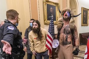 FILE - In this Wednesday, Jan. 6, 2021 file photo, supporters of President Donald Trump, including Jacob Chansley, right with fur hat, are confronted by U.S. Capitol Police officers outside the Senate Chamber inside the Capitol in Washington. Congress is set to hear from former security officials about what went wrong at the U.S. Capitol on Jan. 6. That's when when a violent mob laid siege to the Capitol and interrupted the counting of electoral votes. Three of the four testifying Tuesday resigned under pressure immediately after the attack, including the former head of the Capitol Police. (AP Photo/Manuel Balce Ceneta, File)