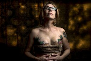 (Leah Hogsten  |  The Salt Lake Tribune) Andrea Reynolds, who had a double mastectomy in 2013, shows the artistry of Fallen Angel Tattoos founder and owner Terrina Francis, Friday, April 20, 2018 in her home. Francis tattooed leaves and branches over Reynolds' reconstructive surgery scars in 2014. The all-women tattoo shop specializes in helping  women who have had breast cancer and reconstructive surgery by tattooing art on their bodies to cover scars.