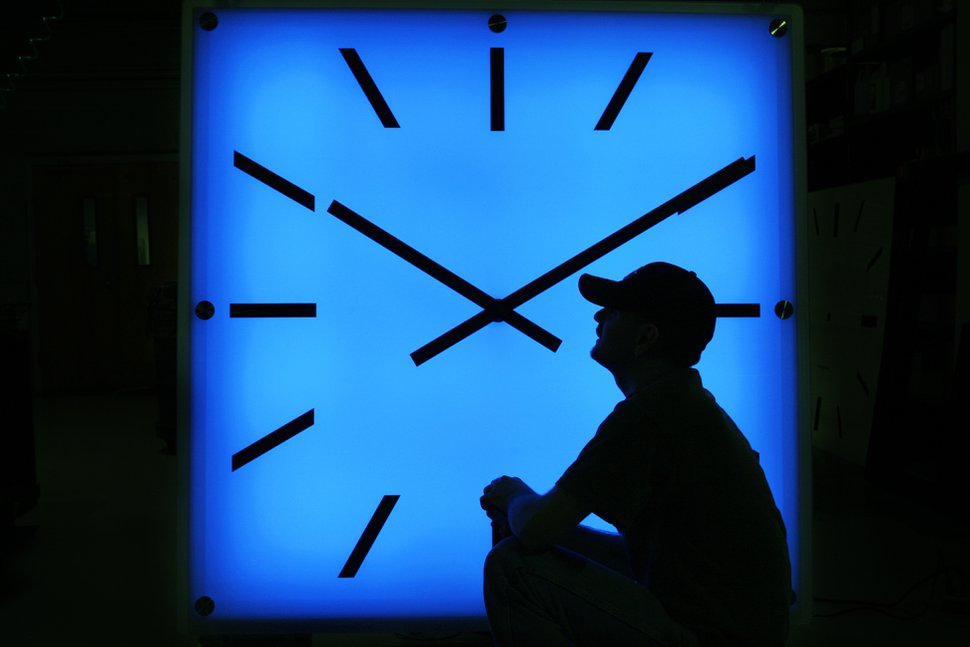 FILE - In this Oct. 30, 2008, file photo, Electric Time Company employee Dan Lamoore adjusts the color on a 67-inch square LED color-changing clock at the plant in Medfield, Mass. As most U.S. residents prepare to