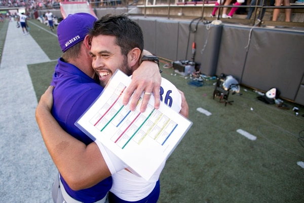 Weber State kicker Josh Kealamakia, right, hugs head coach Jay Hill after booting the game-winning field goal against Montana in an NCAA college football game Saturday, Oct. 10, 2015, in Missoula, Mont. Weber State defeated Montana 24-21 in overtime.(AP Photo/Patrick Record)