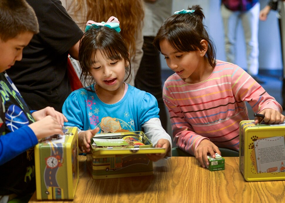 (Leah Hogsten | The Salt Lake Tribune) l-r Siblings Jonathan Escobar, Elizabeth Escobar and Diana Escobar like their new lunch boxes and what's inside them, Tuesday, March 13, 2018 during a food pantry dedication at their school. Smiths Food & Drug is helping to open a food pantry at David Gourley Elementary School in Kearns, where 80 percent of the 646 students qualify for free or reduced lunches.