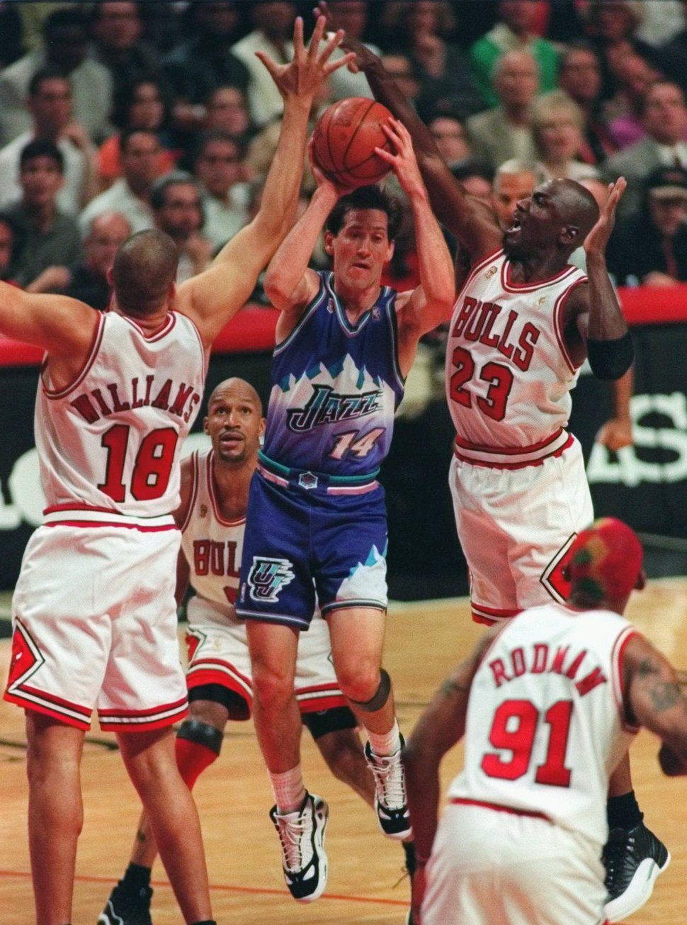 Utah Jazz guard Jeff Hornacek slips between Chicago Bulls' Brian Williams (18) and Michael Jordan (23) during the first quarter of Game 6 of the NBA Finals on Friday, June 13, 1997, in Chicago. Watching are the Bulls' Dennis Rodman and Ron Harper, rear. (AP Photo/Michael Conroy)