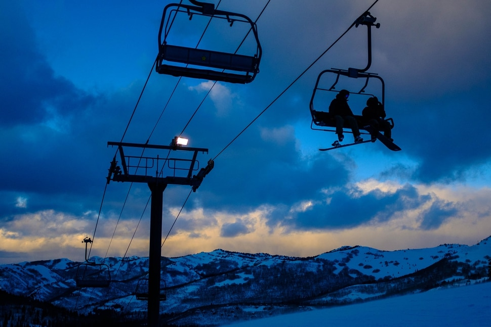 (Trent Nelson | The Salt Lake Tribune) Snowboarders on a lift as night sets in at Brighton on Monday, Feb. 24, 2020.
