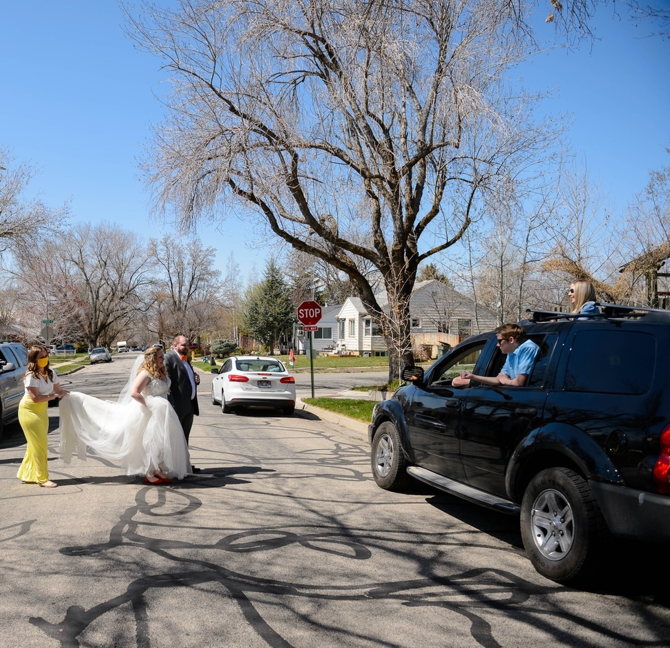 (Trent Nelson | The Salt Lake Tribune) Newlyweds Kadie and Tyler van Roosendaal cross the street to greet friends and family who watched the wedding from their vehicle, in Salt Lake City on Saturday, April 4, 2020.
