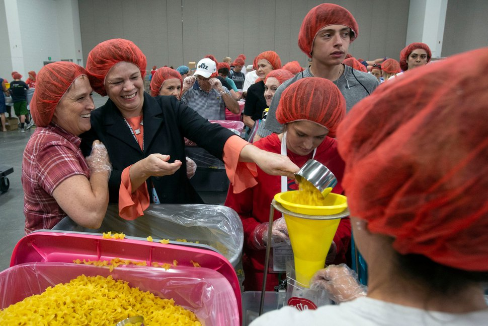 (Photo courtesy of The Church of Jesus Christ of Latter-day Saints) Sharon Eubank, president of Latter-day Saint Charities, helps volunteers fill bags with pasta during a service project at the 68th United Nations Civil Society Conference in Salt Lake City, Monday, Aug. 26, 2019.