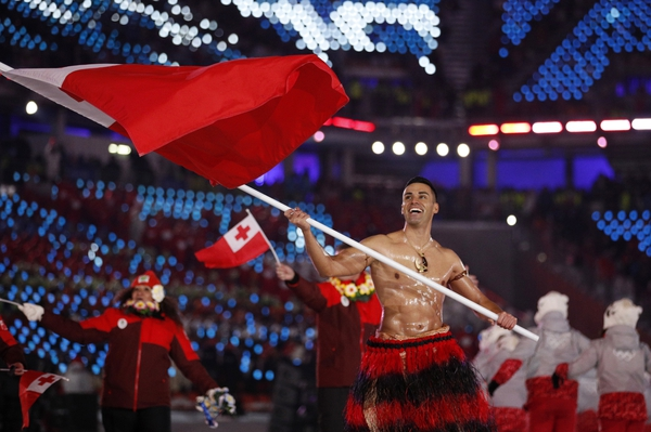 FILE - In this Feb. 9, 2018 file photo, Pita Taufatofua carries the flag of Tonga during the opening ceremony of the 2018 Winter Olympics in Pyeongchang, South Korea. Taufatofua has more on his mind than just trying to compete at the Pyeongchang Olympics this week. The 34-year-old cross-country skier is concerned about his homeland after it was hit by a cyclone which destroyed Parliament House as well as churches and homes. (AP Photo/Jae C. Hong, File)