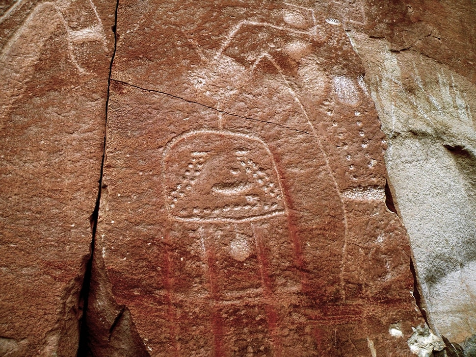 (Erin Alberty|The Salt Lake Tribune) Fremont petroglyphs show a character holding what appears to be a severed head at McConkie Ranch in Dry Fork Canyon near Vernal. Photo taken July 23, 2009.