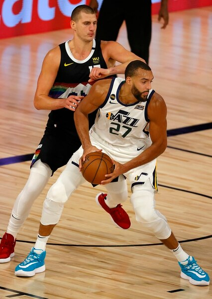 Rudy Gobert, right, of the Utah Jazz drives the ball against Nikola Jokic, left, of the Denver Nuggets during the first half of Game 5 of an NBA basketball first-round playoff series, Tuesday, Aug. 25, 2020, in Lake Buena Vista, Fla. (Mike Ehrmann/Pool Photo via AP)