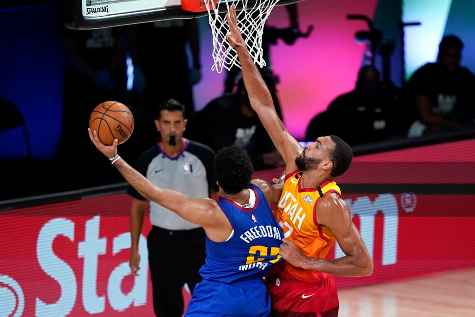 Utah Jazz's Rudy Gobert, right, grabs the jersey of Denver Nuggets' Jamal Murray as he shoots during the second half of an NBA basketball first round playoff game Sunday, Aug. 30, 2020, in Lake Buena Vista, Fla. (AP Photo/Ashley Landis)