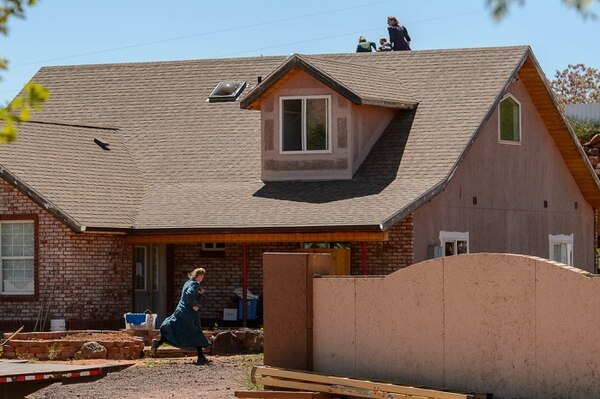 Trent Nelson   The Salt Lake Tribune An FLDS woman runs away and another scurries her children off the roof as Mohave County Constable Mike Hoggard arrives to post a second eviction notice on a Colorado City, AZ, home, Monday May 1, 2017.