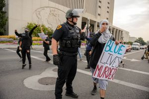 (Trent Nelson  |  The Salt Lake Tribune) Protesters walk through a police line on State Street in Salt Lake City on Saturday, Aug. 22, 2020.
