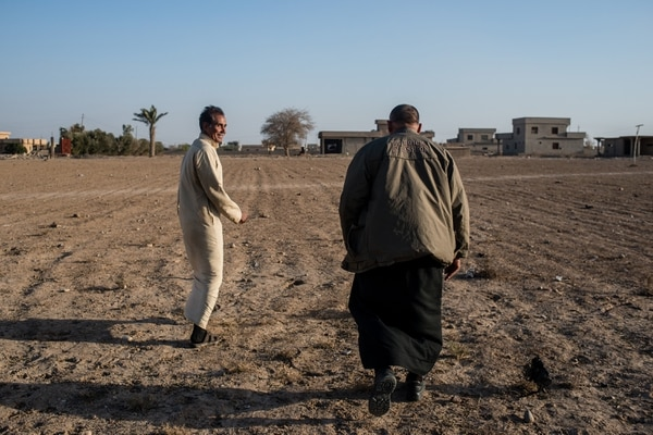 (Alex Potter | The Washington Post) Ibrahim and Yaseen al-Agedi, brothers, examine the land they farm in Ijhala, Iraq. They fear that when growing season arrives, the soil, dried from sulfur, will no longer produce crops.