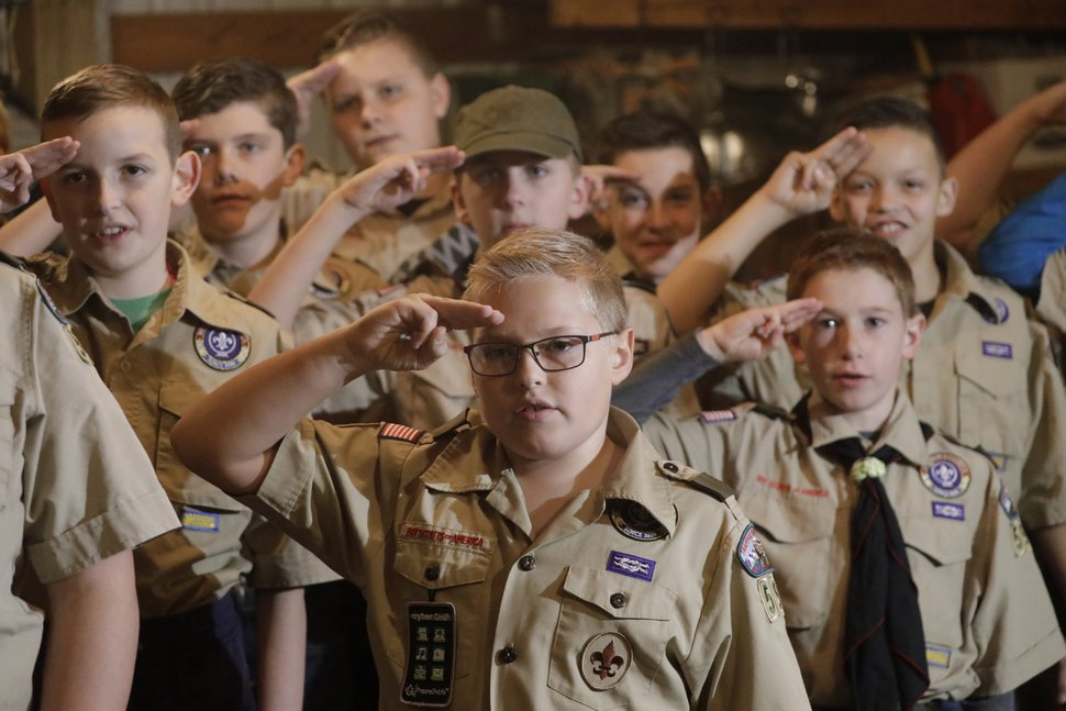 (Rick Bowmer | The Associated Press) Boy Scouts salute during their meeting, in Kaysville on Thursday, Dec. 12, 2019,
