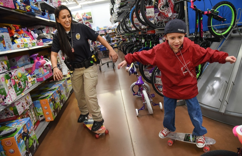 (Francisco Kjolseth | The Salt Lake Tribune) Officer Tiana Hunter tries her skateboarding skills alongside Austin Quinney, 8. The Salt Lake County Sheriff's Office and Unified Police took 100 children Christmas shopping in Riverton as part of its Shopping with the Shield program on Saturday, Dec. 15, 2018.