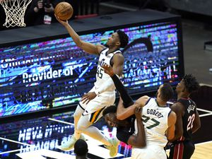 Utah Jazz guard Donovan Mitchell (45) goes to the basket as center Rudy Gobert (27) defends Miami Heat center Bam Adebayo, center, during the first half of an NBA basketball game, Friday, Feb. 26, 2021, in Miami. (AP Photo/Lynne Sladky)