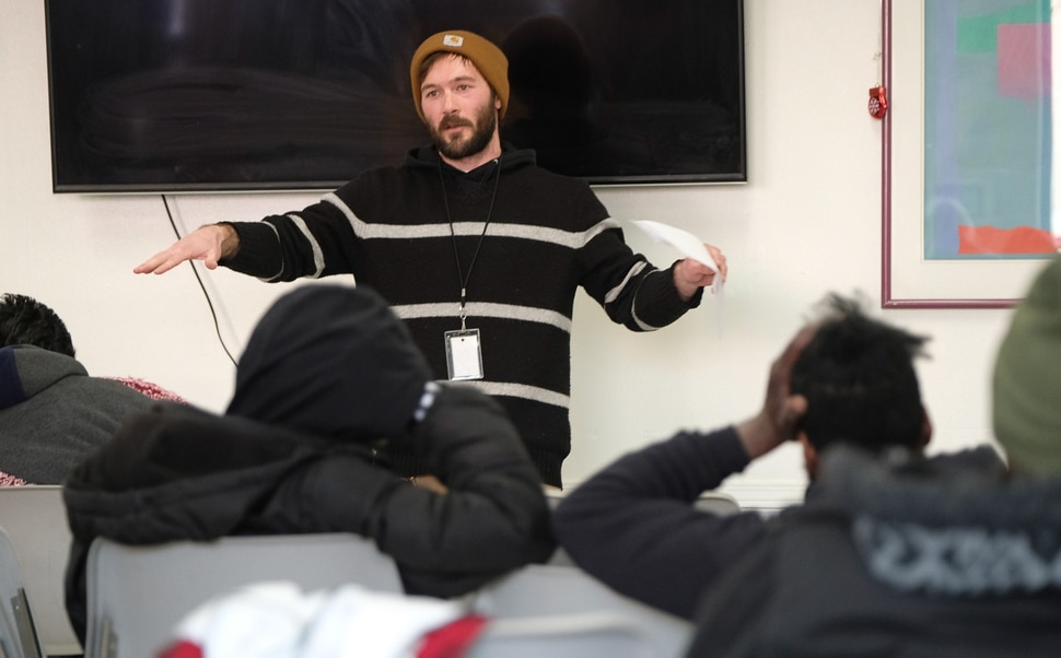 (Francisco Kjolseth | The Salt Lake Tribune) Joe Pace, Employment and Life Skills Coordinator leads a town hall meeting in the day room of the Weigand Center on Wednesday, Dec. 18, 2019, where Catholic Community Services hosts the weekly event to get more input from its homeless clients. In the back of the room there is a survey kiosk that asks clients about service, cleanliness and what people would like to see to better serve them.
