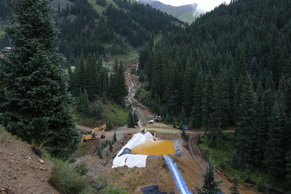 Water flows through one in a series of retention ponds built to contain and filter out heavy metals and chemicals from the Gold King mine wastewater accident, in the spillway about 1/4 mile downstream from the mine, outside Silverton, Colo., Wednesday, Aug. 12, 2015. The Environmental Protection Agency has taken full responsibility for the mine waste spoiling rivers downstream from Silverton, but people who live near the idled and leaking Gold King mine say local authorities and mining companies spent decades spurning federal cleanup help. (AP Photo/Brennan Linsley)