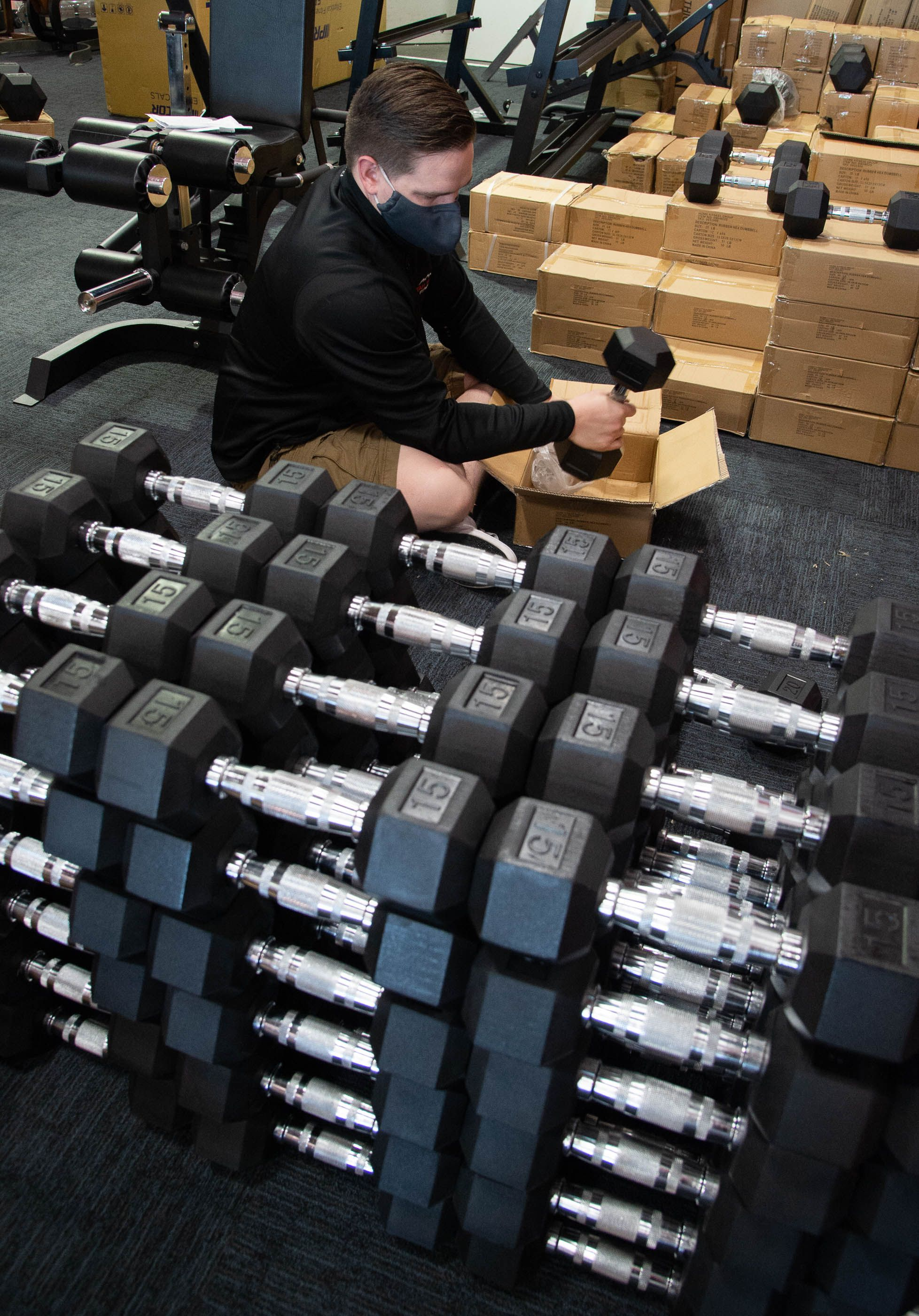 (Francisco Kjolseth  |  The Salt Lake Tribune) Chase Buckles, sales manager at Utah Home Fitness in Sandy, takes advantage of a slow moment to catch up on restocking inventory on Wednesday, Oct. 22, 2020. Home fitness equipment sales boomed in March and April when gyms closed because of the coronavirus. Everything from inexpensive dumbbells to premium treadmills and ellipticals were wiped out of stores and warehouses. Record sales continue throughout the summer — normally the slow time for the industry, and store owners expect sales to remain high during the holidays.
