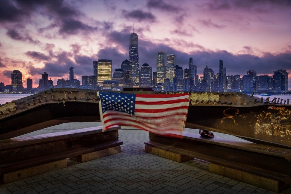 (J. David Ake   AP Photo) A U.S. flag hanging from a steel girder, damaged in the Sept. 11, 2001 attacks on the World Trade Center, blows in the breeze at a memorial in Jersey City, N.J., Sept. 11, 2019 as the sun rises behind One World Trade Center building and the re-developed area where the Twin Towers of World Trade Center once stood in New York City on the 18th anniversary of the attacks.
