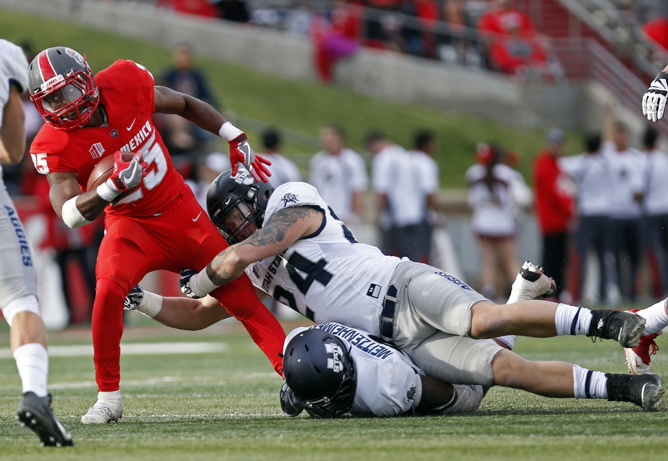 New Mexico running back Tyrone Owens (25) is stopped by Utah State linebacker Dalton Baker (24) and linebacker Kevin Meitzenheimer during the first half of an NCAA college football game in Albuquerque, N.M., Saturday, Nov. 4, 2017. (AP Photo/Andres Leighton)