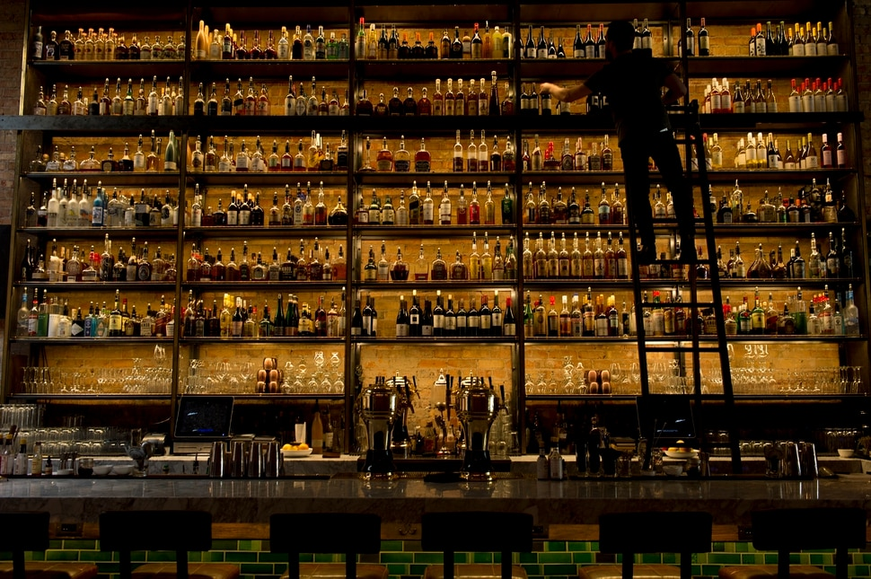 (Leah Hogsten | The Salt Lake Tribune) White Horse Spirits and Kitchen bartender Sam Wood restocks the shelves behind the bar.