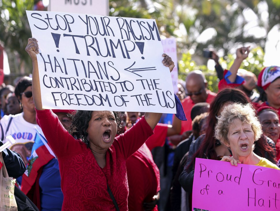 FILE- This Jan. 15, 2018, file photo shows Haitian community supporters in West Palm Beach, Fla., to protest remarks made by President Donald Trump about Haiti. The NAACP has sued the U.S. Department of Homeland Security. The organization says Trump's disparaging comments about immigrants and their home countries is evidence of racial discrimination that has influenced his administration's decision to end protections for roughly 60,000 Haitians. (Damon Higgins/Palm Beach Post via AP, File)