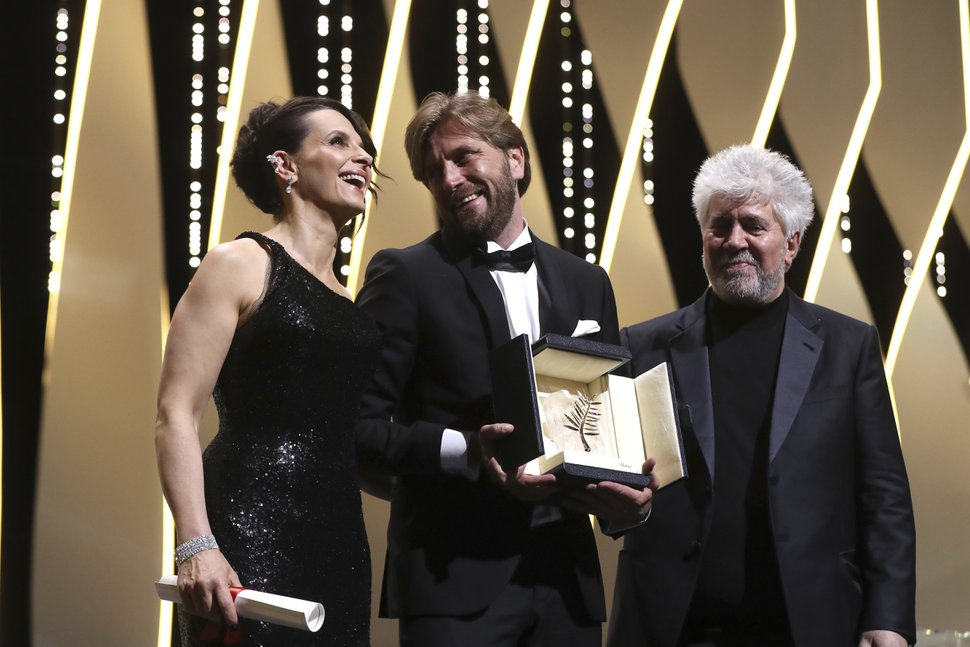 Director Ruben Ostlund, centre, with his Palme d'Or award for his film The Square, presented by actress Juliette Binoche, left, and jury president Pedro Almodovar during the awards ceremony at the 70th international film festival, Cannes, southern France, Sunday, May 28, 2017. (AP Photo/Alastair Grant)