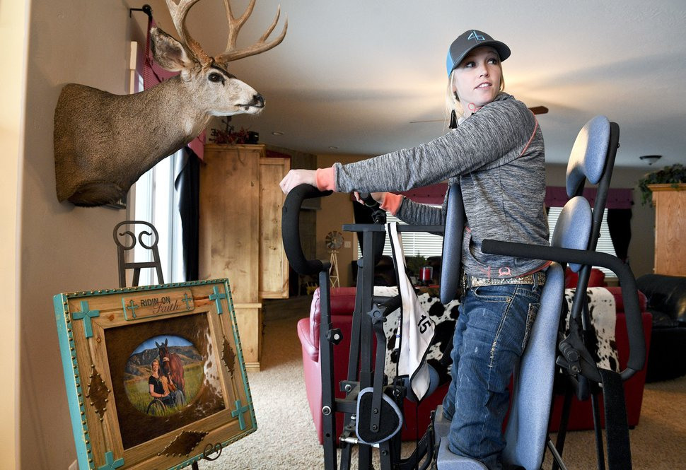 (Isaac Hale | The Daily Herald file photo) In this Jan. 5, 2017, file photo, Amberley Snyder uses her standing frame as she talks with her family at her home in Elk Ridge, Utah. The standing frame allows Snyder to stand, and the handles allow her to simulate a walking motion that circulates blood flow and works her leg muscles. Not everyone can say they've been a stunt double in a feature film. But that's exactly what Utah State University alumna Snyder, partially paralyzed professional barrel racer, is able to say now that she has finished filming
