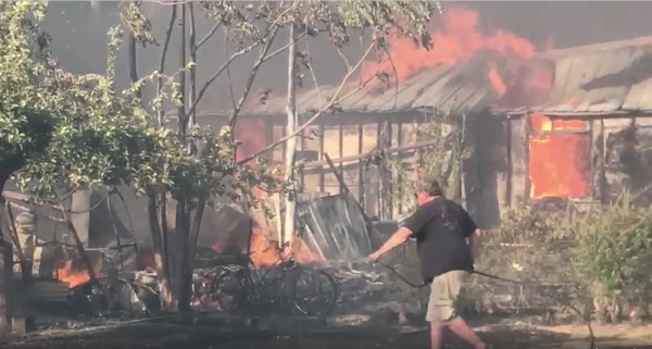 (Courtesy image from video filmed by Kevin Sheets) A Moab resident uses a garden hose to wet a lawn near a wildfire that raged through a neighborhood near Pack Creek on Tuesday night, destroying eight homes, two garages and a shop.