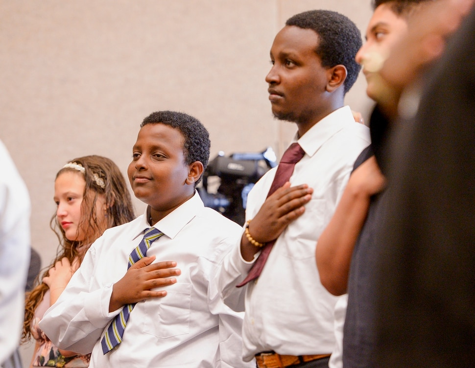 Leah Hogsten | The Salt Lake Tribune l-r With hands on their hearts brothers Michael and Biruk Mekonnen and other youth, ages 5 to 22, representing 8 countries, spoke the oath of citizenship as America's newest citizens during a youth naturalization ceremony at the Viridian Event Center in West Jordan, Monday, August 6, 2018.