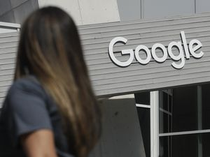 (Jeff Chiu   AP file photo)  In this Sept. 24, 2019, file photo a woman walks below a Google sign on the campus in Mountain View, Calif.
