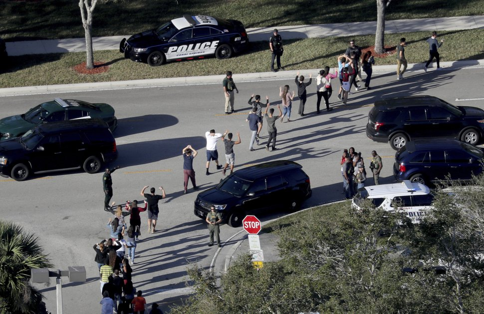 FILE - In a Wednesday, Feb. 14, 2018 file photo, students hold their hands in the air as they are evacuated by police from Marjory Stoneman Douglas High School in Parkland, Fla, after a shooter opened fire on the campus. Frustration is mounting in the medical community as the Trump administration again points to mental illness in response to yet another mass shooting. (Mike Stocker/South Florida Sun-Sentinel via AP, File)
