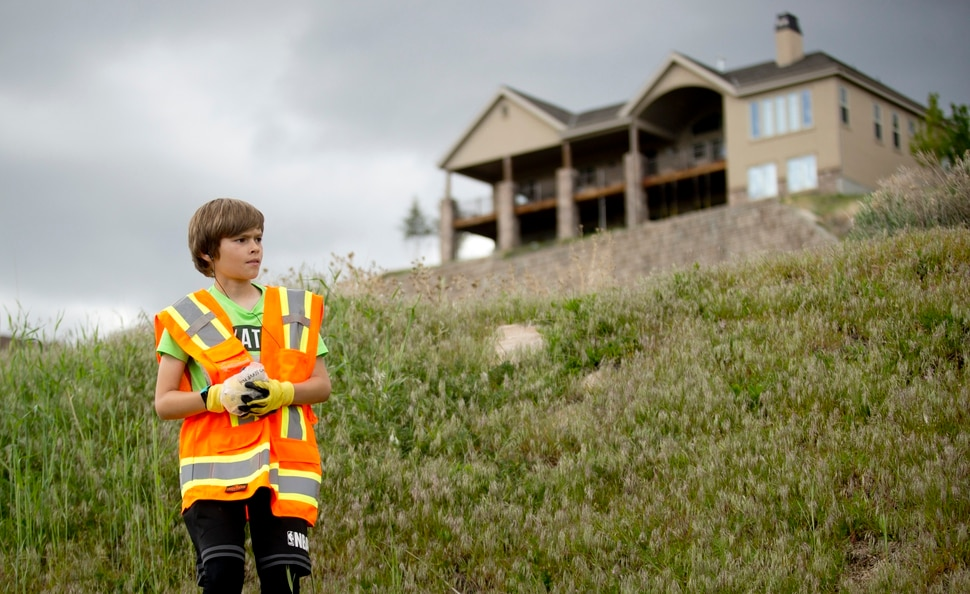 In a Wednesday, May 8, 2019 photo, Damon Haub, 10, of Lehi, gathers up trash as he and other volunteers help to complete an Eagle Scout Service Project that aims to create a walkable path connecting nearby neighborhoods to Ignite Entrepreneurship Academy and a future park, just northwest of the charter school in Lehi, Utah. (Isaac Hale/The Daily Herald via AP)