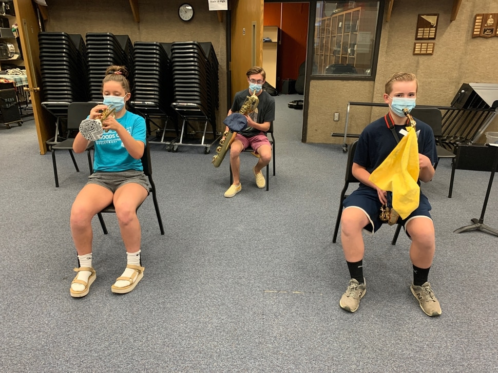 (Photo courtesy of Todd Campbell) Woods Cross High School band students practice on covered wind and brass instruments while wearing masks.