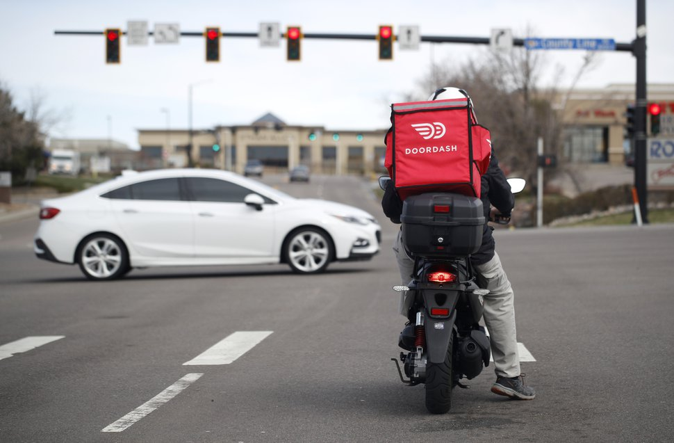 (David Zalubowski | AP file photo) A food delivery rider waits for the traffic light to change Monday, March 30, 2020, in Lone Tree, Colo.