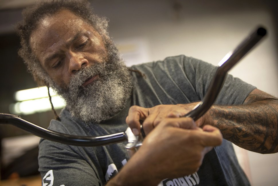 In this Tuesday, Aug. 7, 2018 photo, Mark Johnson attaches new handlebars to one of his homemade bikes at the Ogden Bicycle Collective in Ogden, Utah. Johnson took mechanic classes at the non-profit bike collective before he started building his own bicycles. (Benjamin Zack/Standard-Examiner via AP)