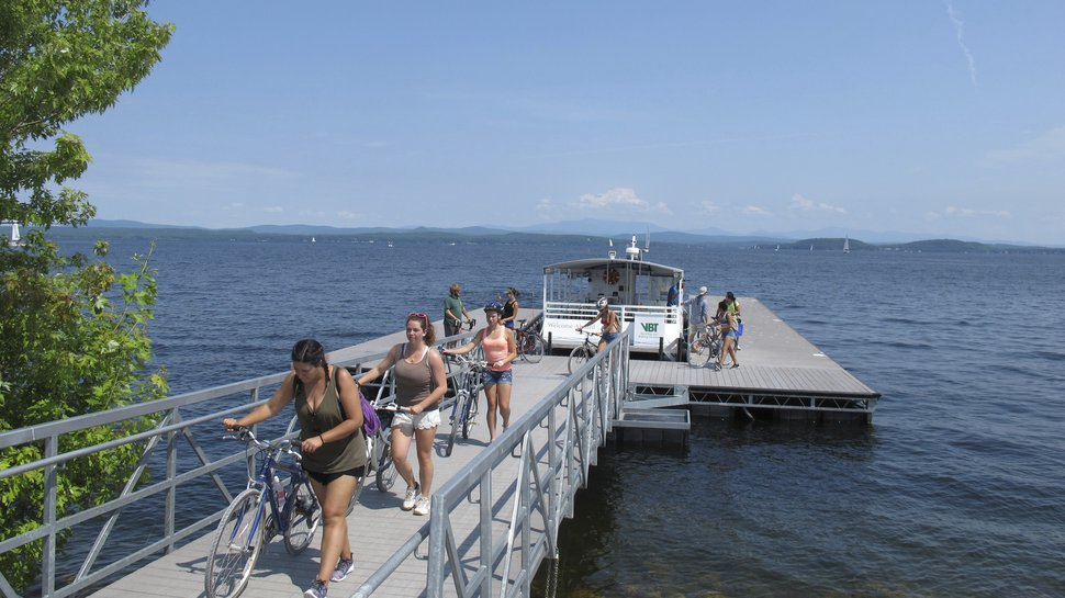 In this July 22, 2017 photo taken in South Hero, Vt., bicyclists walk their bikes after getting off a special ferry across a cut in an abandoned railroad causeway from the Vermont mainland to the Lake Champlain islands. The seasonal ferry on the three-mile section of the Island Line Trail bike path carries cyclists across the opening in the causeway so they can reach the islands. (AP Photo/Wilson Ring)
