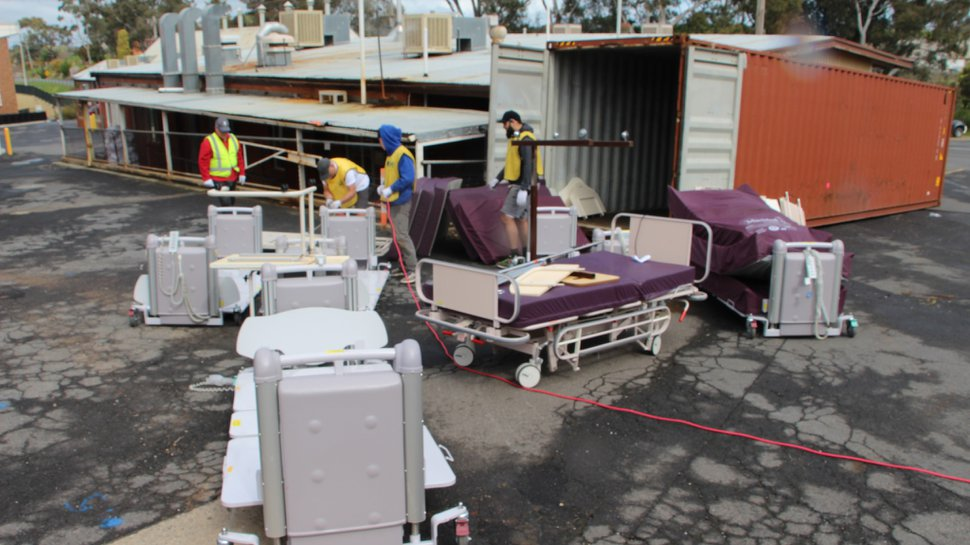 (Photo courtesy of The Church of Jesus Christ of Latter-day Saints) Workers load more than 130 donated hospital beds into shipping containers in Melbourne, Australia. The beds will be used at Port Moresby General Hospital in Papua New Guinea.