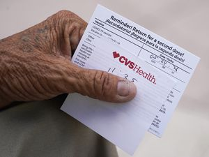 (AP Photo  Wilfredo Lee) A man holds his vaccination reminder card after having received his first shot at a pop-up vaccination site in the Little Havana neighborhood of Miami.