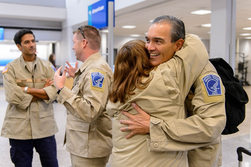 (Trent Nelson | The Salt Lake Tribune) Chad Pascua and Laura Tramell embrace as members of Utah's DMAT-1 (Disaster Medical Assistance Team) meet at the Salt Lake City Airport en route to Texas, Tuesday August 29, 2017. 36 members of the team are headed to the Houston area to help with the fallout of Hurricane Harvey.