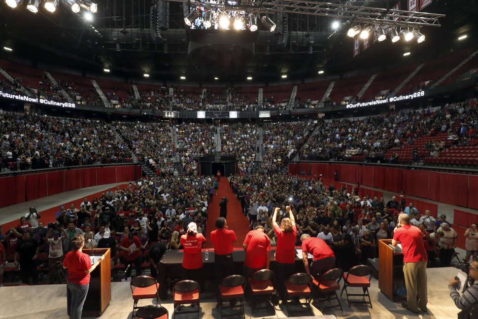 Members of the Culinary Workers Union, Local 226, assemble for a presentation in a university arena before an evening vote on whether to authorize a strike Tuesday, May 22, 2018, in Las Vegas. A potential strike would affect 34 casino-hotels. A majority yes vote will not immediately affect the casinos, but it gives union negotiators a huge bargaining chip by allowing them to call for a strike at any time starting June 1. (Steve Marcus/Las Vegas Sun via AP)