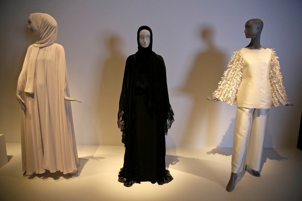 In this photo taken Thursday, Sept. 20, 2018, a black silk and lace Dolce & Gabbana ensemble, center, is displayed in the exhibit Contemporary Muslim Fashions at the M. H. de Young Memorial Museum in San Francisco. The first major museum exhibition of contemporary Muslim women's fashion reflects designs from around the world that are vibrant and elegant, playful and diverse. The show's creators hope the exhibit will show Muslim women as real people who can choose what they wear rather than as subjects ordered to cover their entire bodies or restricted in what they can wear. The exhibit opens on Saturday. (AP Photo/Eric Risberg)